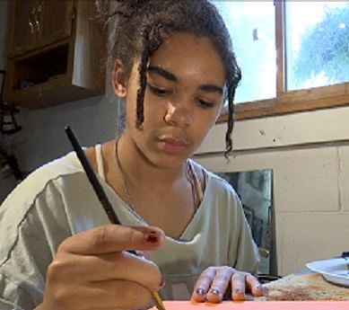 Young artist painting on canvas