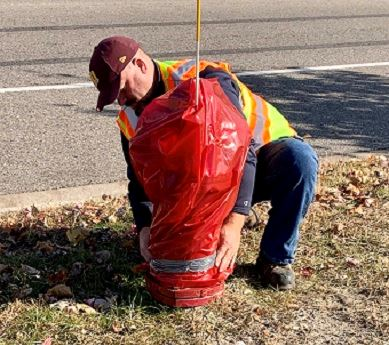 Worker places a red plastic bag over a fire hydrant